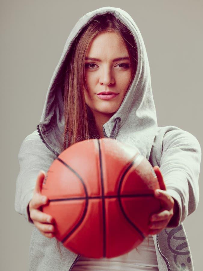 Sporty предназначенная для подростков девушка в клобуке держа баскетбол стоковые изображения