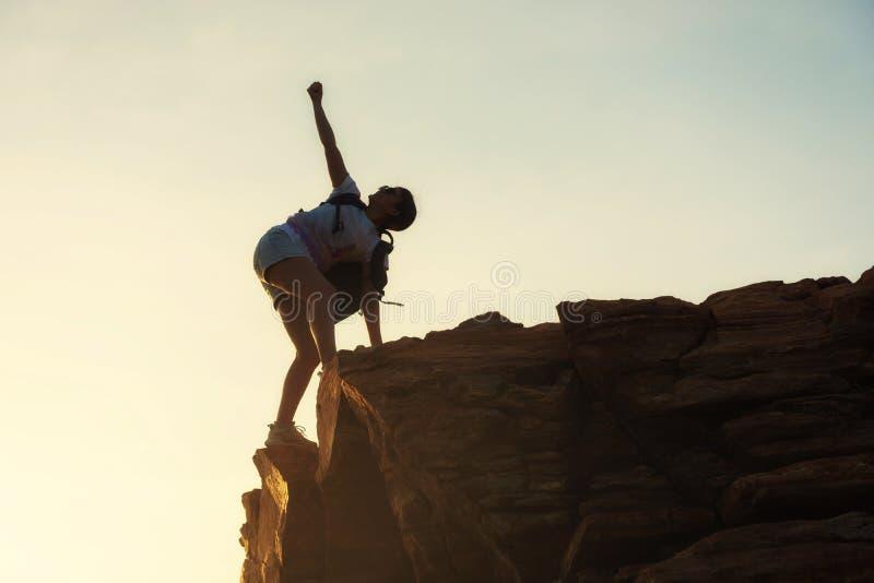 Sporty рука повышения женщины на горном пике стоковые изображения rf