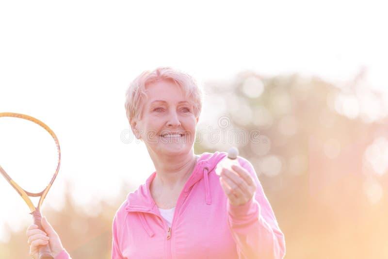 Sporty старшая женщина играя бадминтон с ракеткой тенниса в парке стоковые изображения
