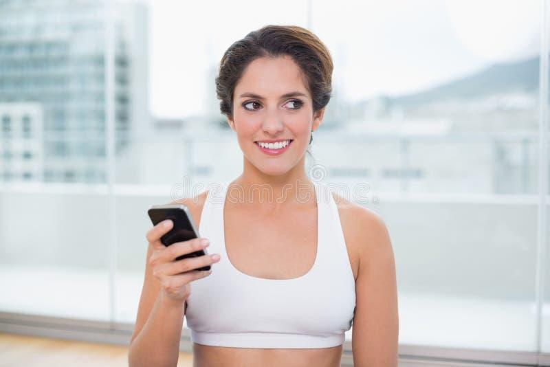 Sporty счастливое брюнет держа smartphone стоковые изображения