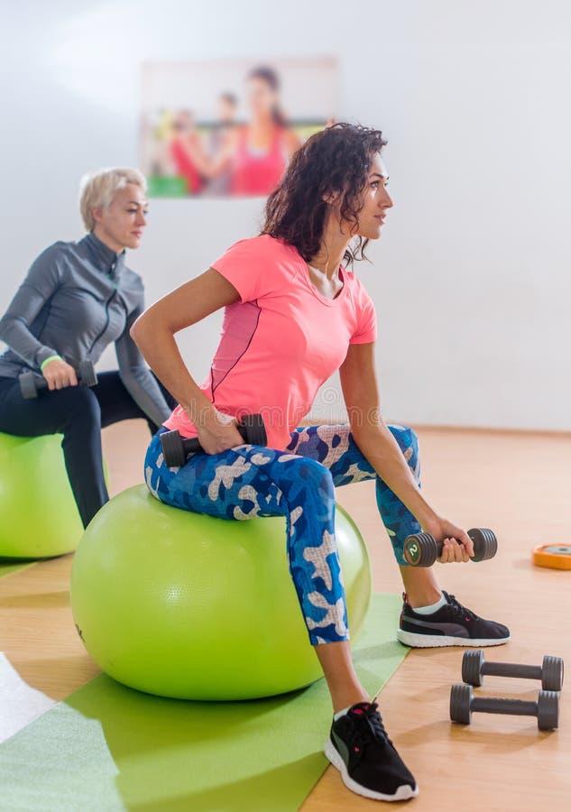 Sporty тонкие женщины принимать класс фитнеса спортзала работая сидеть на physioballs делая, который чередуют бицепсы завивают с стоковые фото