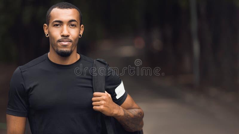 Sporty человек представляя после разминки, нося черная футболка стоковое изображение rf