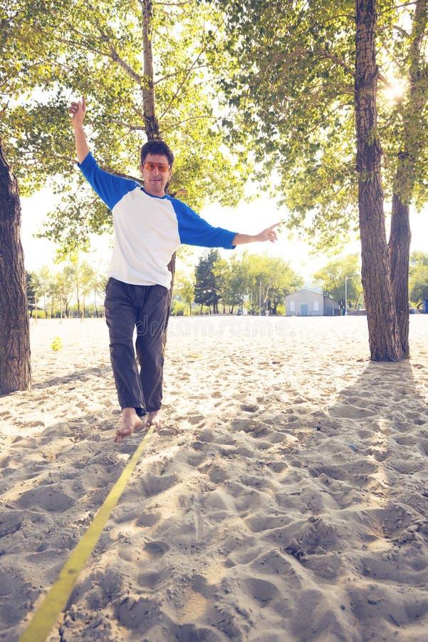 Sporty человек, с смешной стороной, идет на slackline стоковое изображение