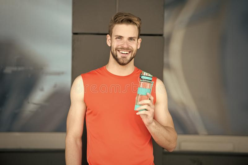 Sporty accessory. Man athlete hold special sporty bottle care hydration body after workout. Refreshing vitamin drink. Athlete drink water after training. Man royalty free stock images