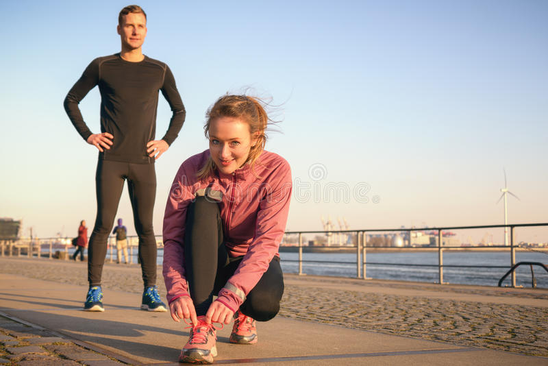 Sporty active couple on a seafront promenade. Getting ready to go for a jog in their daily workout with the attractive young women bending down to tie her laces stock photos
