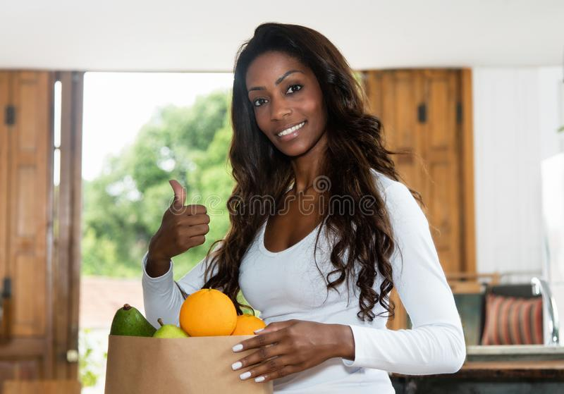 Sporty african american woman with fresh and healthy fruits stock image
