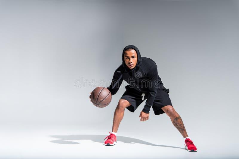 sporty amerykanina afrykańskiego pochodzenia mężczyzna bawić się z koszykówki piłką i patrzeje kamerę obrazy stock