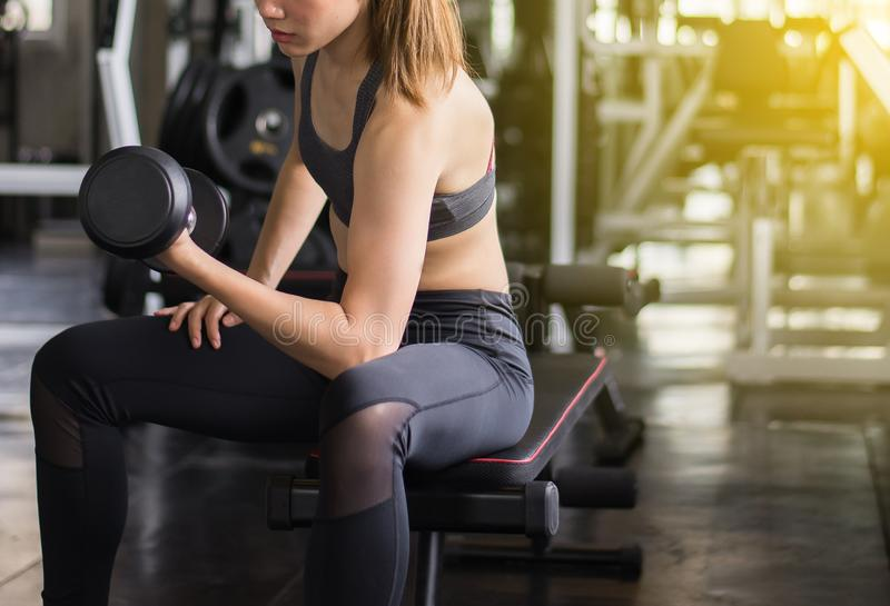 Sporty asian beautiful woman exercise with dumbbell,Female in sportswear does the exercises at fitness center stock photo