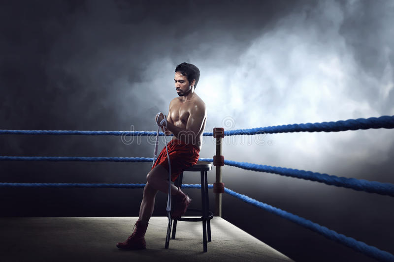 Sporty asian boxer man sitting on ring while wearing strap. On wrist stock photos