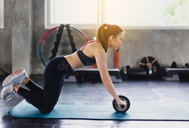 Sporty asian woman doing workout and exercise with roller wheel for balance body at the gym center,Individual sport stock photos