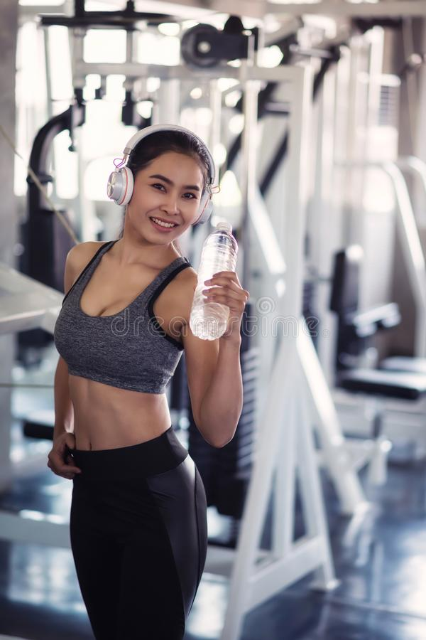 attractive woman hold bottle of water in gym stock images