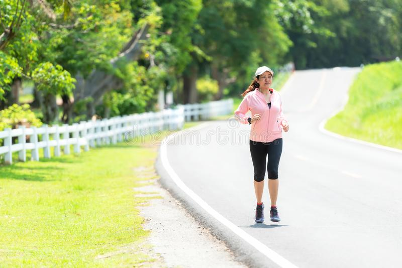 Sporty asian woman runner running and jogging through the road. Outdoor Workout in a Park. Weight Loss and Healthy Concept royalty free stock photos