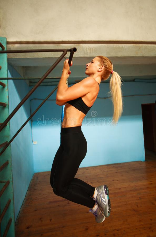 Sporty athlete woman exercising doing pull-ups in gym from back stock photos