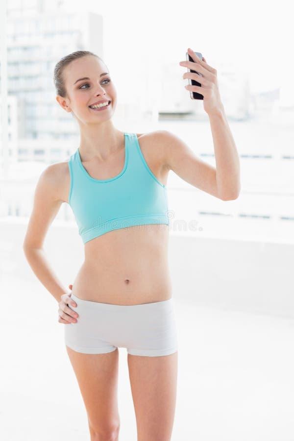 Sporty atrakcyjna kobieta ono uśmiecha się przy smartphone zdjęcia royalty free