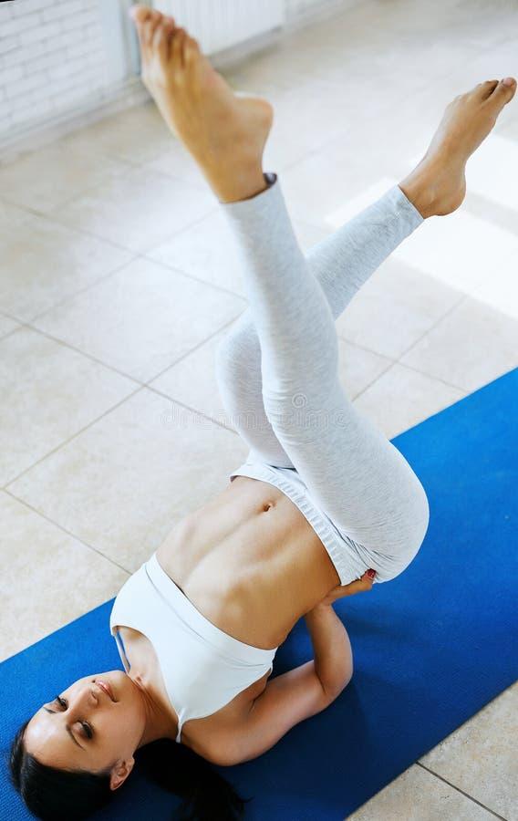 Sporty atrakcyjna młoda brunetki kobieta robi joga ćwiczeniu w pokoju z białymi ścianami Zdrowy styl życia, ranek obraz royalty free