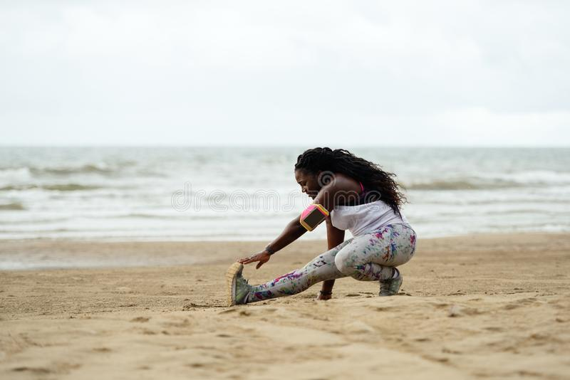 Sporty attractive african woman doing exercises on the beach stock photo