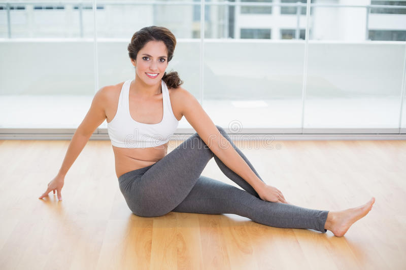 Sporty attractive brunette stretching on the floor stock photos