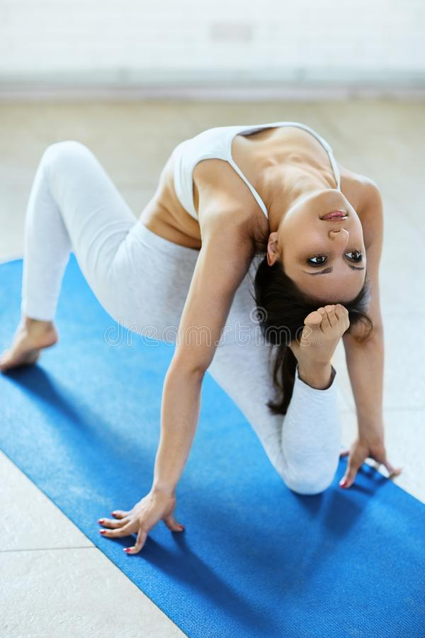Sporty attractive young brunette woman doing yoga asana for back and leg, sitting on the mat in a gym with white wall royalty free stock photography