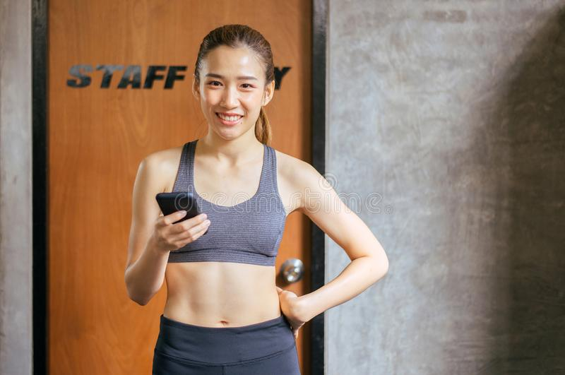 Sporty beautiful asian woman posture standing and holding mobile phone and exercises muscle at gym,Happy and smiling royalty free stock photography