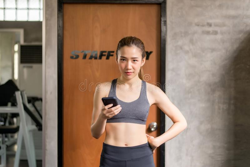 Sporty beautiful asian women using smart phone at gym,Happy and smiling. Sporty beautiful asian woman using mobile phone at gym,Happy and smiling royalty free stock images
