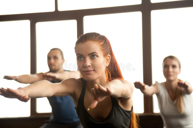 Sporty beautiful redhead girl doing fitness exercise at group tr royalty free stock images