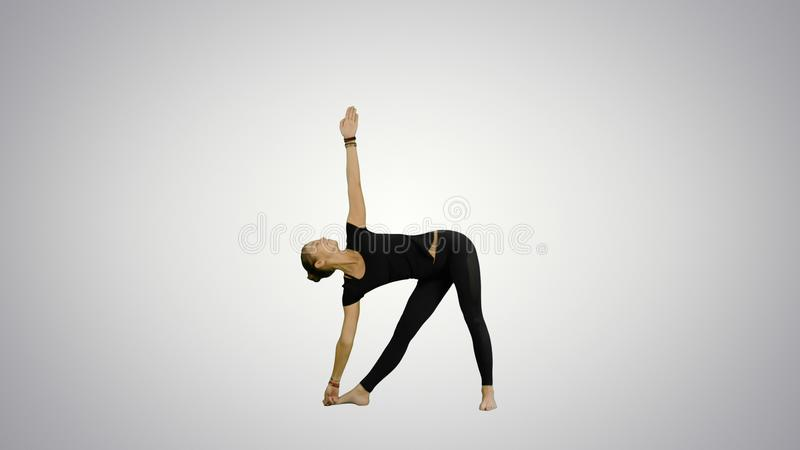 Sporty beautiful smiling young woman standing in Utthita Trikonasana, extended Triangle Pose on white background. Professional shot in 4K resolution. 078. You royalty free stock image