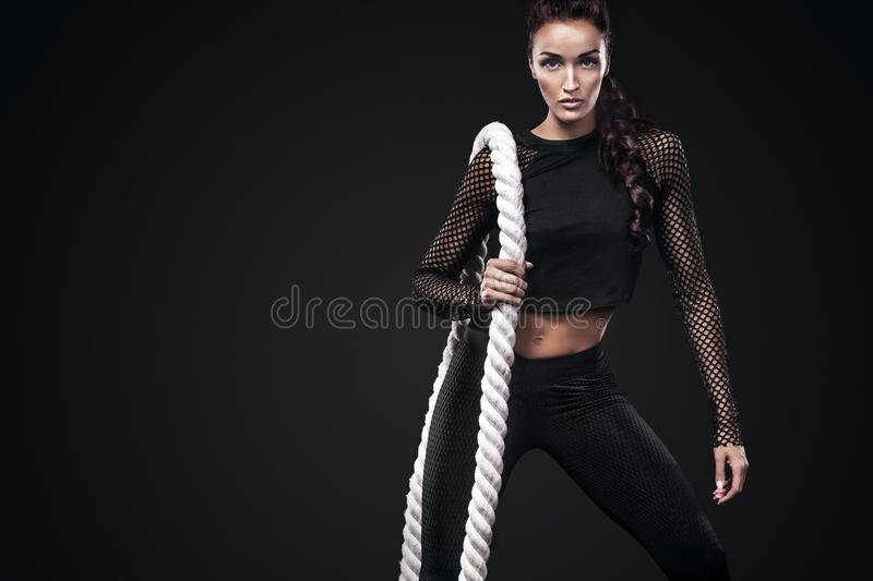 Sporty beautiful woman with battle rope makes fitness exercising at black background to stay fit stock image
