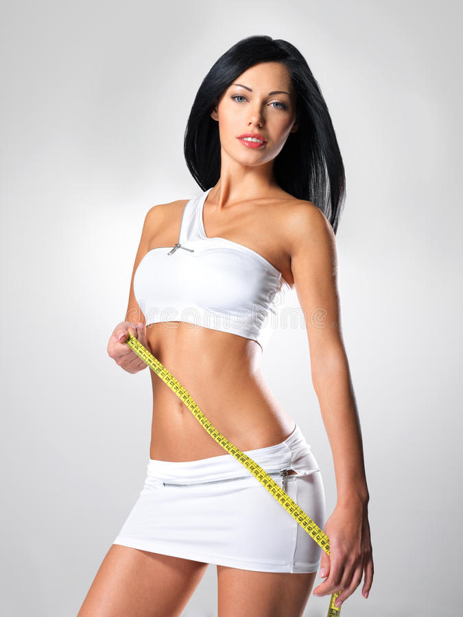 Sporty beautiful woman with measure tape stock photo