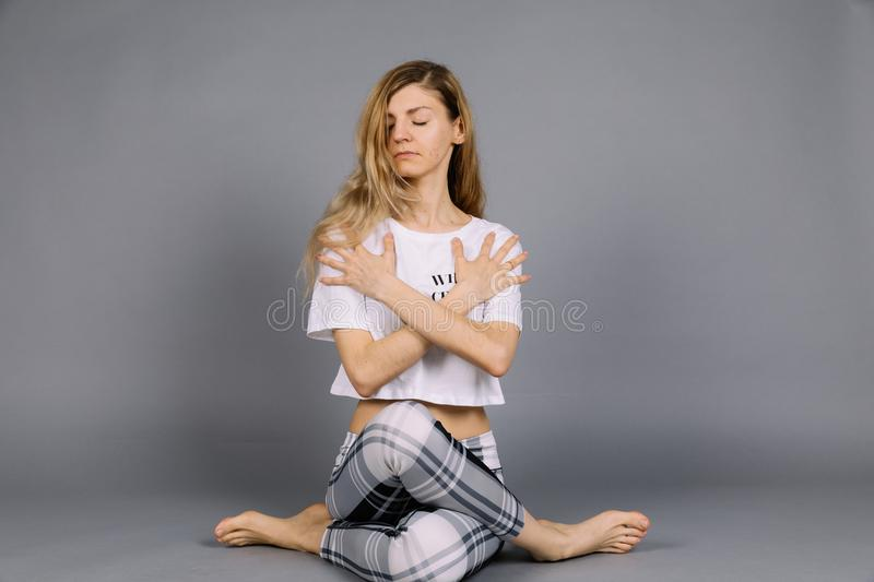 Sporty beautiful young woman practicing yoga, working out wearing grey and white sportswear, studio, full length stock image