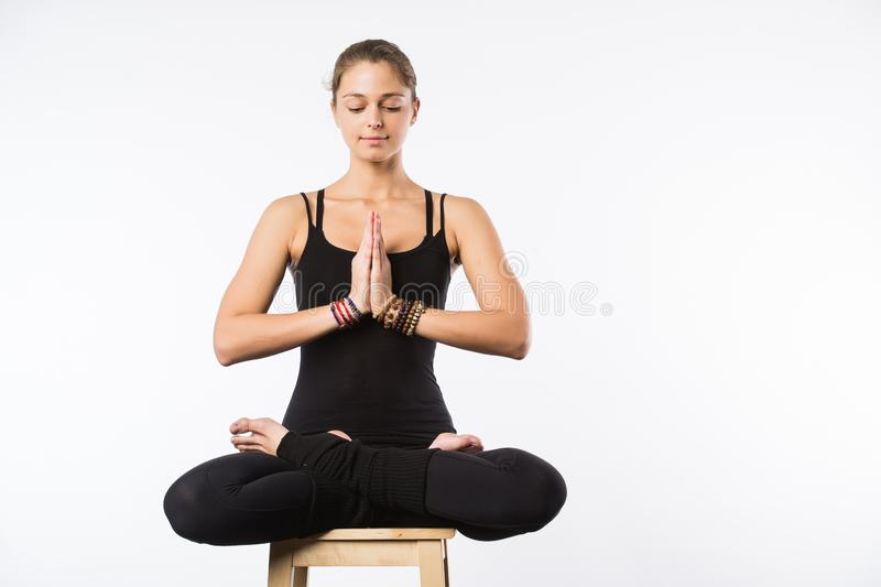 Sporty beautiful young woman sitting in Gomukhasana, Cowface pose, yin yoga Shoelace posture, asana for stretching hips royalty free stock photography