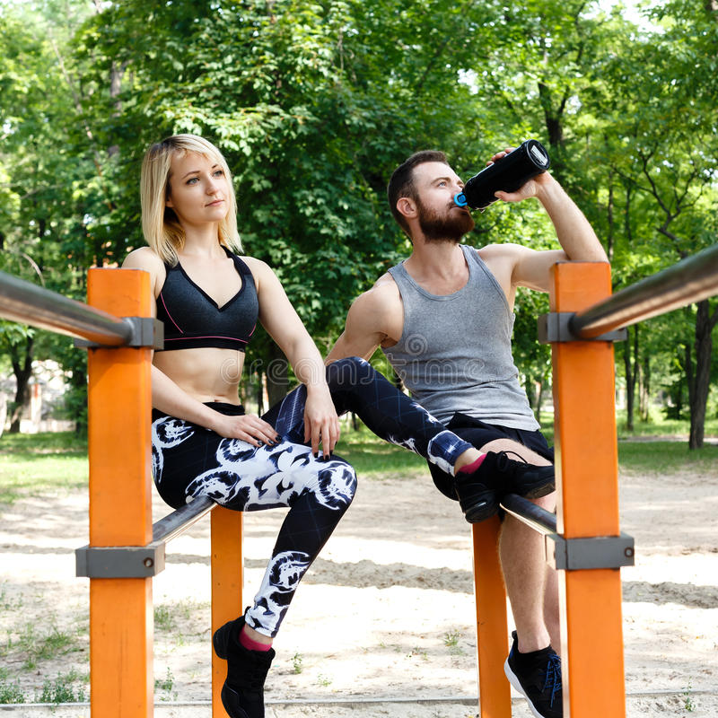 Sporty blonde girl and bearded man is resting after workout training in a park outdoor. Man drinking water from a black bottle. royalty free stock image