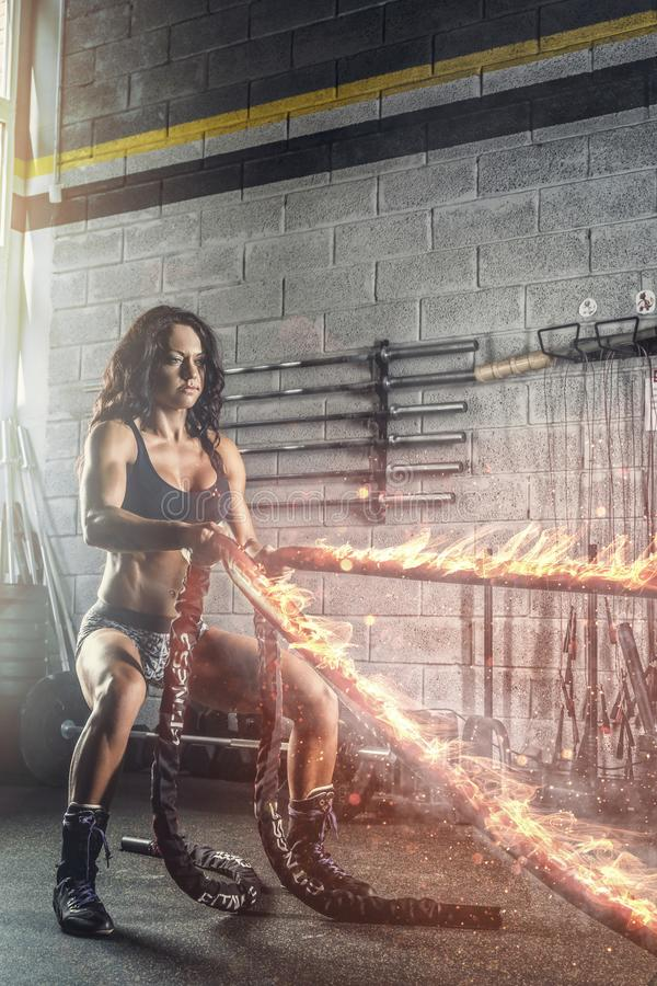 Sporty brunette female exercising with burning battle rope. stock photos