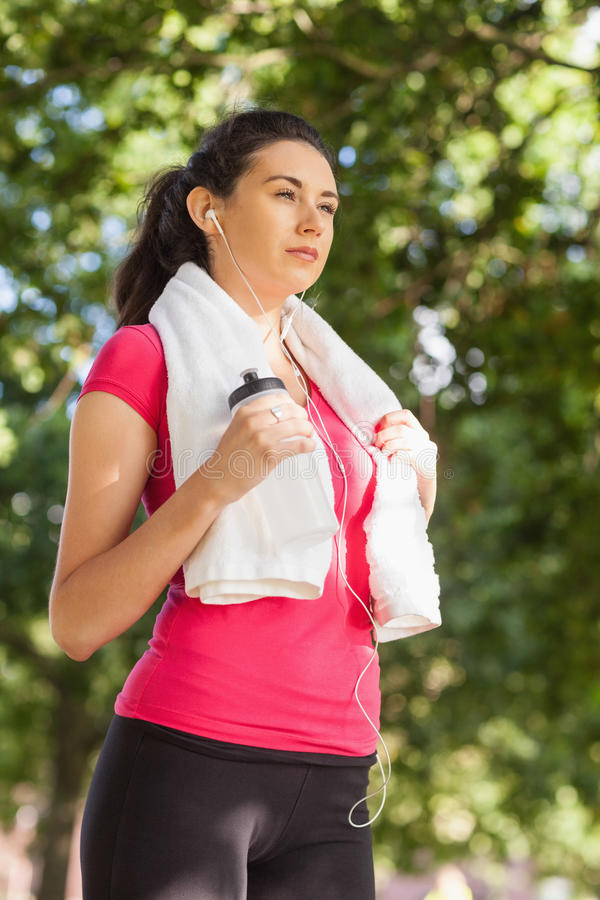 Sporty brunette woman posing while holding a towel royalty free stock photography