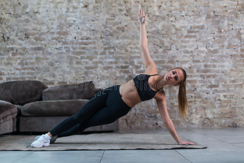 Sporty Caucasian girl doing side plank star exercise working abs and oblique muscles indoors against brick wall royalty free stock photos