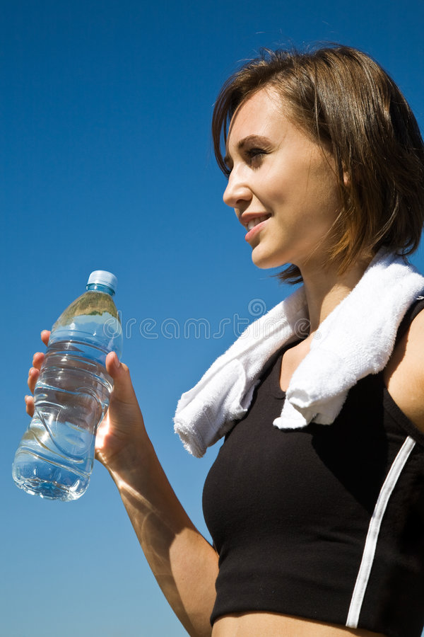 Sporty caucasian girl with water bottle. A beautiful sporty caucasian girl carrying a water bottle after exercise on the beach stock photos
