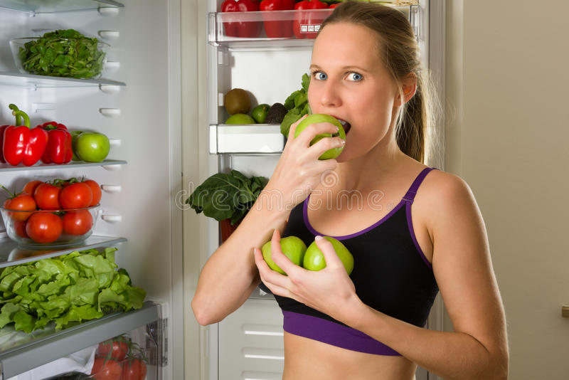 Sporty, Caucasian woman biting a green apple for healthy eating stock photography