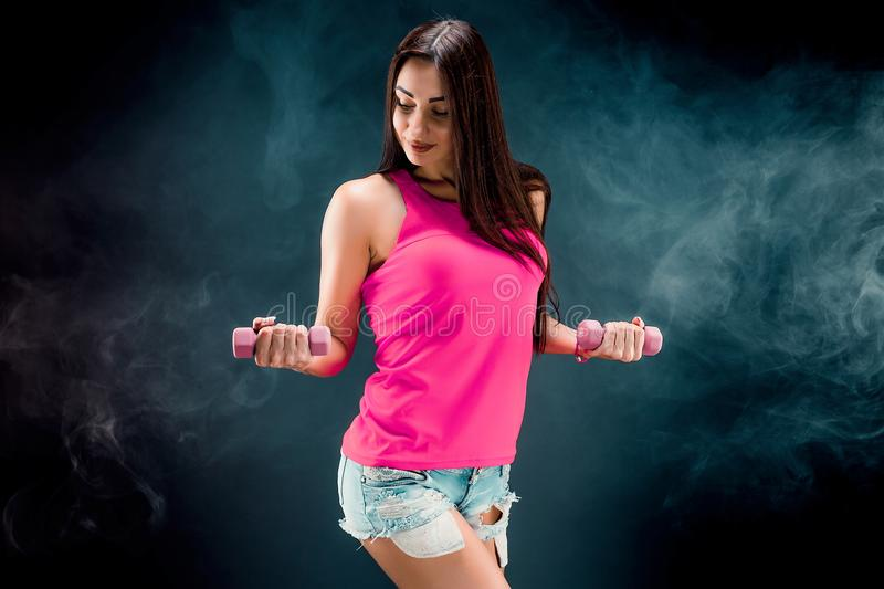 Sporty caucasian woman posing with dumbbells in studio. And looking down royalty free stock photos