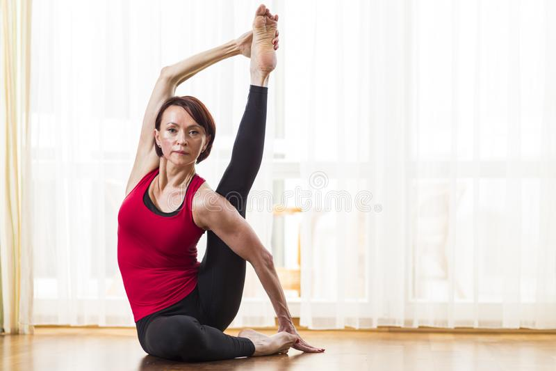 Sporty Caucasian Woman Practicing Yoga Asana Indoors in Front of Big Sunny Window. Doing Stretching Exercises In Therapy Pose. Horizontal Image royalty free stock images