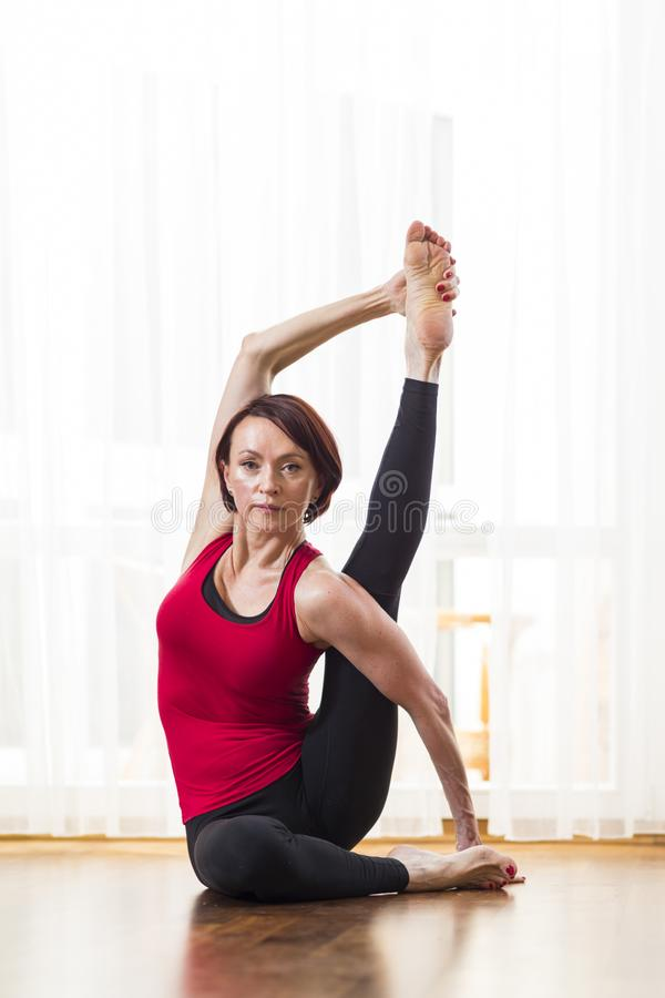 Sporty Caucasian Woman Practicing Yoga Asana Indoors in Front of Big Sunny Window. Doing Stretching Exercises In Therapy Pose. Vertical Shot stock photo
