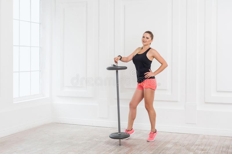 Sporty concept. Satisfied athletic young beautiful blonde girl in pink top and black shorts standing, holding barbell and showing stock image