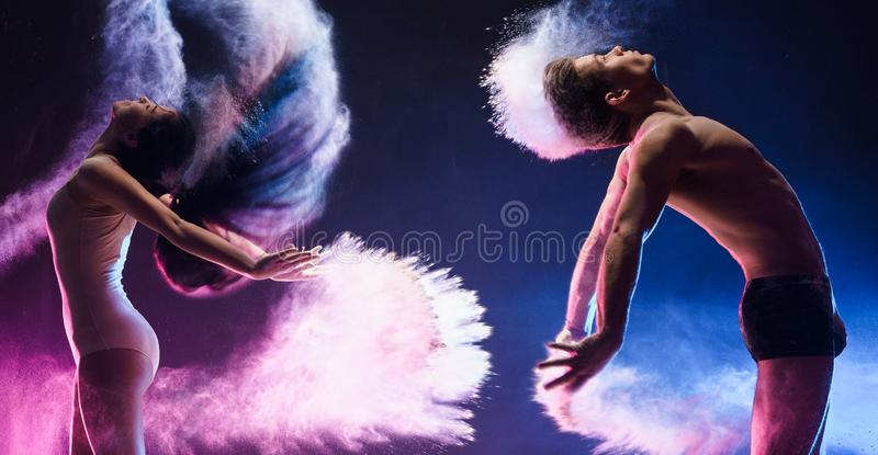 Sporty couple in color dust cloud studio shot. Young sporty men and slim women posing emotionally in jump in cloud of pink and blue dust studio portrait royalty free stock image
