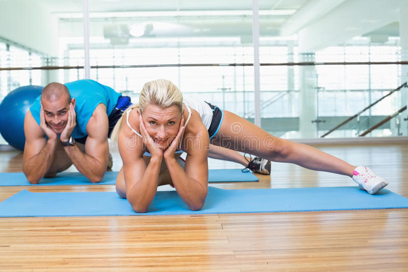 Sporty couple doing pilate exercises at fitness studio stock image