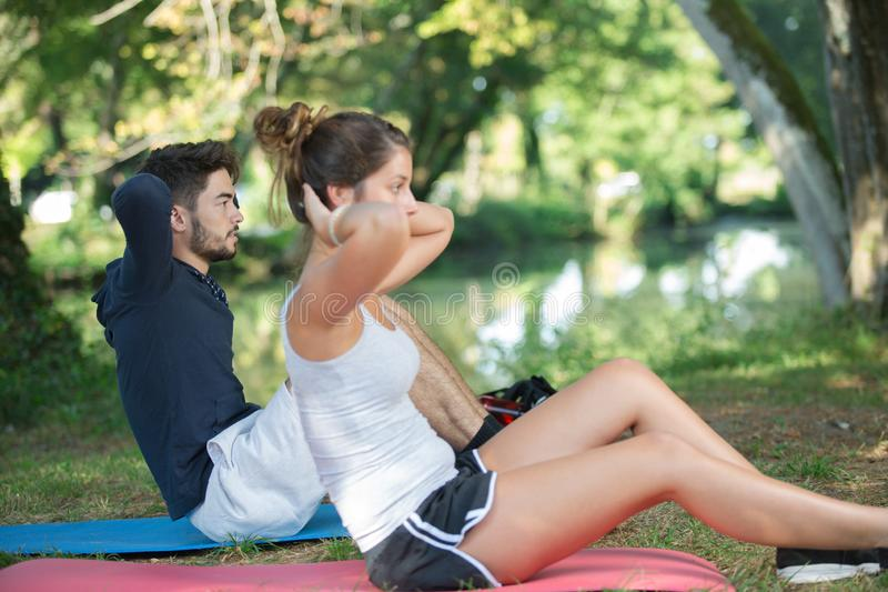 Sporty couple doing sit-ups outdoors stock photography
