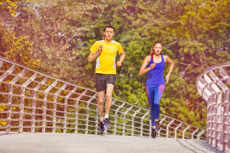 Sporty couple jogging at park in summer royalty free stock images