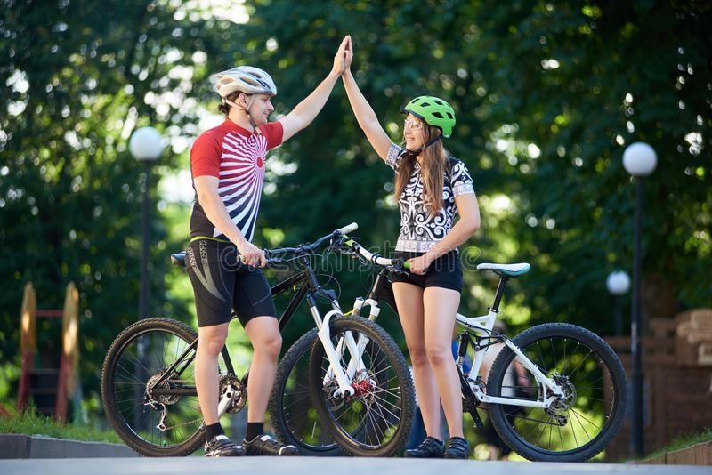 Sporty couple giving high five in park stock photos