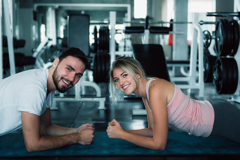 Sporty couple planking exercise in fitness gym., Portrait of attractive young couple are practicing workout in training class., royalty free stock image