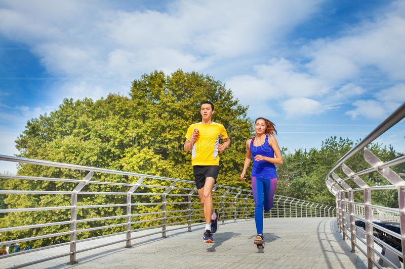 Sporty couple running across a bridge in summer stock photo