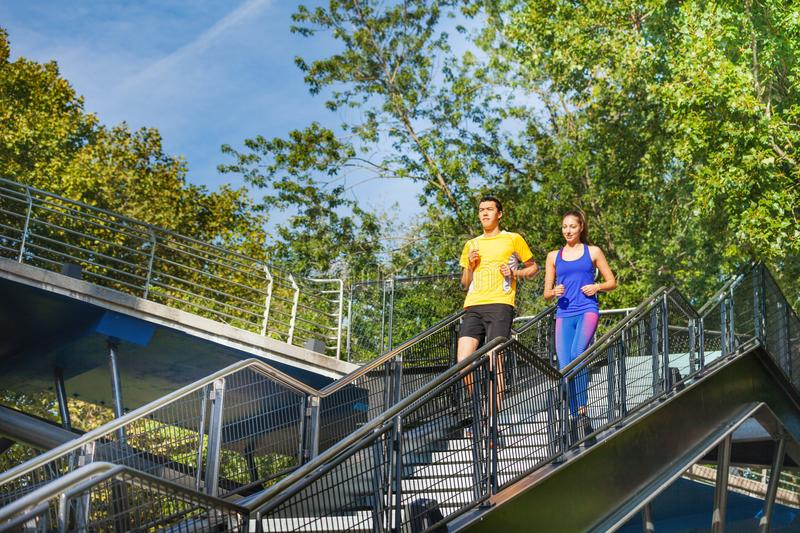 Sporty couple running downstairs at city park royalty free stock photography