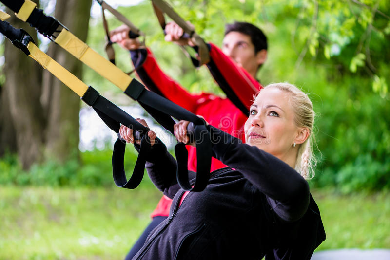 Sporty couple at sling trainer doing fitness stock image
