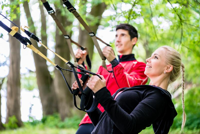 Sporty couple at sling trainer doing fitness. In park stock photography